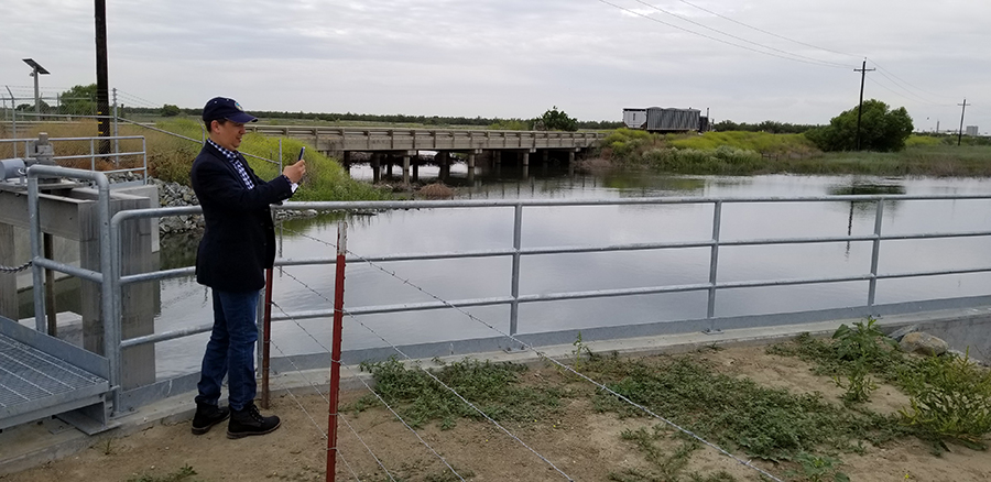 Art Hinojosa, manager of the Department of Water Resources Division of Integrated Water Management, tours the McMullin On-Farm Flood Capture and Recharge Project on the Kings River. In the background are the head gates that divert floodwaters from the river into the project's canal system.
